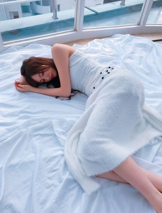 白いワンピースを着た眠ってしまっている梅澤美波の画像