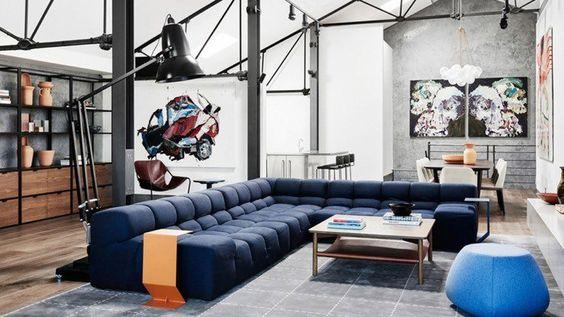 grand canapé matelassé en bleu foncé, lampadaire industriel et peinture effet béton ciré dans le séjour moderne de style loft