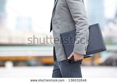 young business man standing with laptop by CHAIWATPHOTOS, via ShutterStock