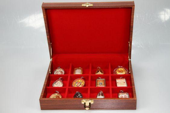 Edle Sammlerbox für 12 Amulette aus deutscher Fertigung. Die Sammlerbox wurde in Deutschland aus europäischen Echtholz hergestellt, Mahagonifarben lackiert und mit zwei goldfarbigen Scharnieren sowie einem goldfarbigen Federverschluss versehen. Im Inneren befindet sich 1 Tablett mit 12 Fächern, die 4,5 cm breit und 4,5 cm hoch sind. In die Fächer passen die meisten Thai Amulette mit und ohne Fassung.