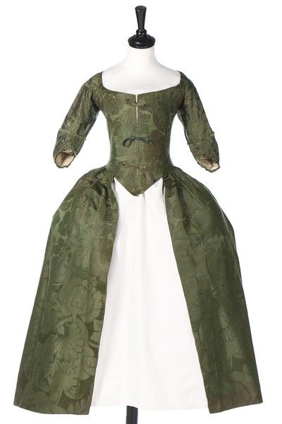 A Spitalfields forest-green damask silk robe a l'Anglaise, circa 1770, the fabric circa 1743, woven with large scale flowerheads, berries and leaves, with ribbon-tied close front bodice, the angular cuffs edged in self-fringing Archive List - Kerry Taylor Auctions