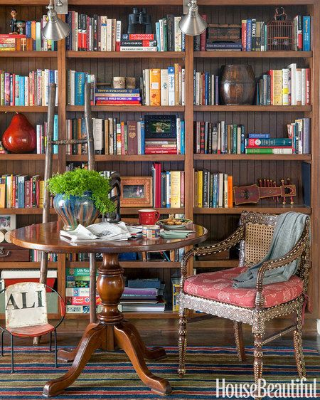 An antique pedestal table and inlaid chair add an Anglo-Indian flavor to an alcove library.: