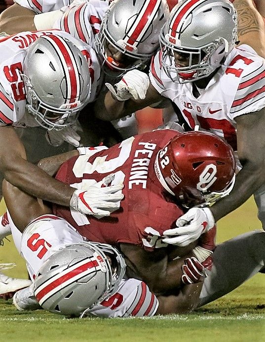 Oklahoma Sooners running back Samaje Perine (32) is gang tackled for a loss by Ohio State defenders Tyquan Lewis (59, Jalyn Holmes (11), Jerome Baker (17), and Raekwon McMillan in the third quarter