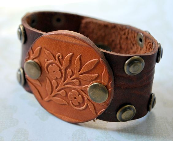 Riveting Floral Leather Cuff Bracelet with Antique Brass by Bandana Girl Rustic textured leather round is riveted to soft and pliable buffalo leather cuff with fun rivets and snap for clasp.  Hand textured and cut dark brown kodiak leather ~ original design by Melinda Orr Feels great on ~ please post exact wrist size for proper fitting. All jewelry comes boxed!Â