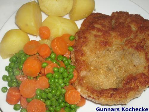 Paniertes Schweineschnitzel mit Kartoffeln und Erbsen und Möhren