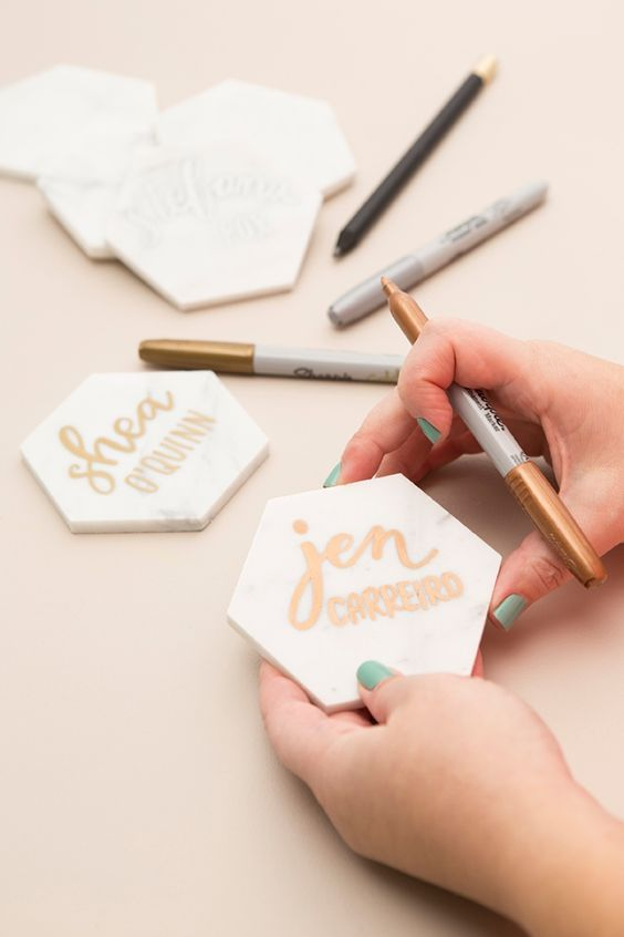 """We used 4"""" white Carrara marble tiles to create these hand-lettered place cards... that double as a gorgeous modern coaster favor for your wedding guests!"""