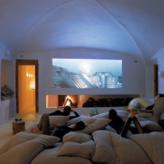 This room is great for everyone to hang out in with the oversized pillows. The fireplace under the screen makes it unique as well and that's definitely a fun way to enjoy your movie.