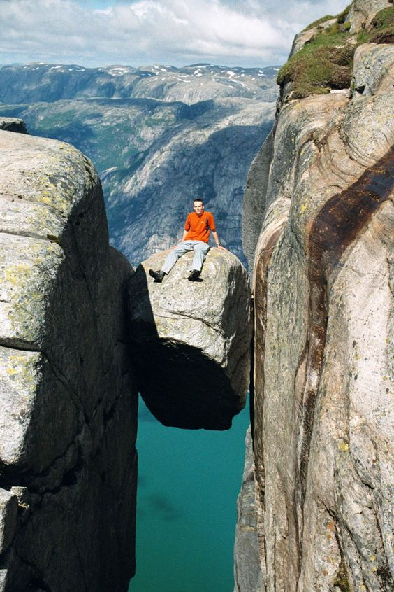 iXiAmazing: Kjeragbolten, a 5 m³ boulder wedged in a mountain crevasse by the edge of the Kjerag mountain, Norway. One can walk onto the rock without any equipment, but there is a direct 241 m drop below and then another tumble of 735 m down to Lysefjorden, so to walk onto it requires good nerves and steady feet!!