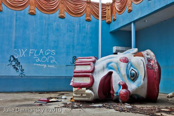 Broken clown head next to abandoned buildings. Six Flags amusement park in Eastern New Orleans, Louisiana, closed since Hurricane Katrina in 2005 remains in a state of ruin.