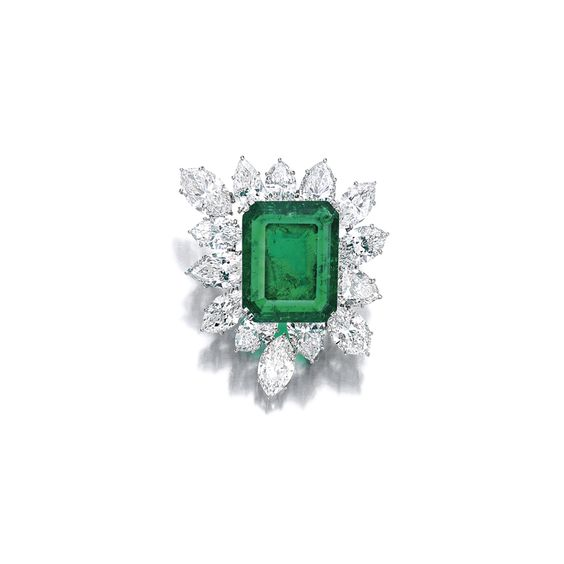 Emerald and Diamond Brooch, Harry Winston Centring on a step-cut emerald weighing 22.21 carats, accented with fourteen pear-and marquise-shaped diamonds weighing 22.54 carats in total, mounted in 18 karat white gold, signed HW.