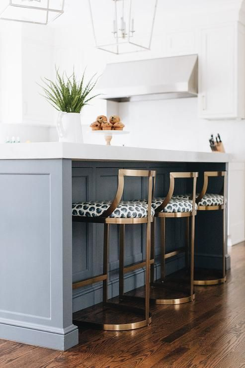 Wisteria Emerson Counter Stools deliver a modern finish at a gray kitchen island topped with white quartz and illuminated with a set of Darlana Lanterns.