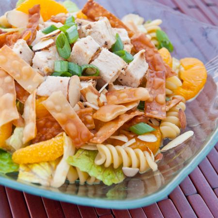 Chicken Wonton Salad    15 small square wonton wrappers  canola oil  2 cups uncooked rotini pasta  2 heads romaine lettuce, chopped  2 cooked chicken breast, diced  6 green onion, diced  ½ cup sliced almonds  2 cans mandarin oranges, drained  sesame ginger dressing (I used Marketside Sesame Ginger Dressing from Walmart)  seasame seeds, optional for garnish