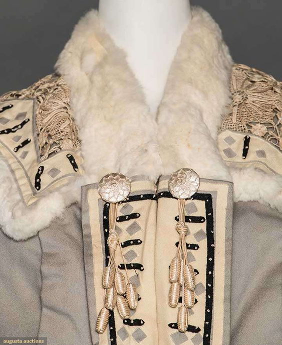"Wool walking suit, ight gray-blue flannel, elaborate jacket trims: torchon lace, diamond cutout cream flannel w/ black appliques & white fur, trained skirt w/ hem pleats, label ""J. Hock Detroit, Mich"", c. 1905"