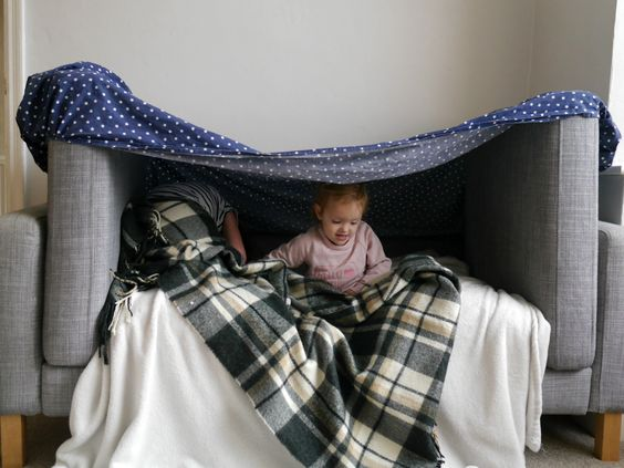 Building a sofa den with small children, AKA a fort. Kids love them!