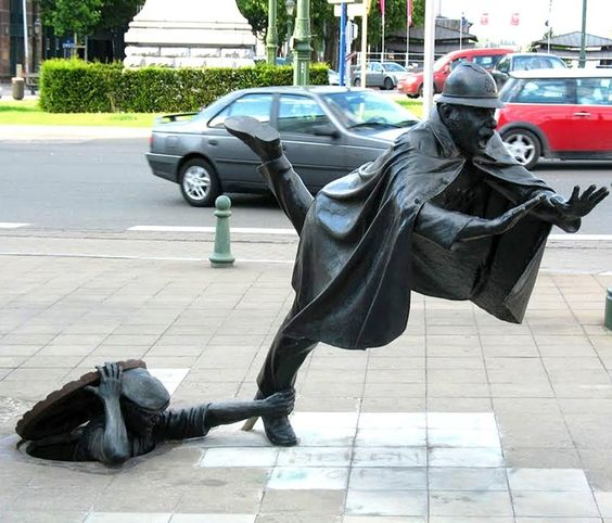 DE VAARTKAPOEN, BRUSSELS, BELGIUM - This Tom Frantzen sculpture is adored by the people of Belgium, it represents someone rising up from the sewers to offset the foot of a passing police officer. Uniquely portraying the struggles of power.