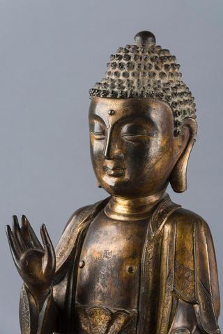 Bouddha en bronze doré, assis en méditation, les mains en vitarka mudra (geste de l'enseignement), les yeux mi-clos donnant au visage une expression de sérenité. Il est vêtu de la robe monastique à décor ciselé de fleurs de lotus. Chine, époque Ming, XVIIème siècle. Hauteur 32 cm.