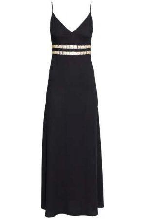 Een lange jurk van een geweven, licht onregelmatige kwaliteit waarin Tencel® lyocell verwerkt is. De jurk heeft een V-hals, cutout details met metalen decoraties in de taille, smalle, verstelbare schouderbandjes en een blinde ritssluiting en een hoge split achter. Ongevoerd.
