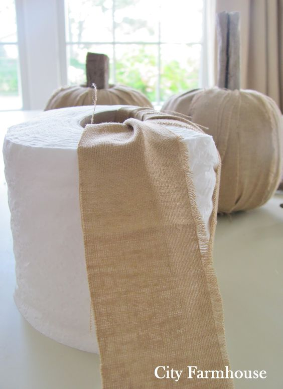"""City Farmhouse: DIY Linen Driftwood Pumpkins -roll of tp, 4 strips fabric (linen, burlap, cotton, duck, drop cloth) 2""""x54"""", driftwood or other for stems in hole.wrap & tuck fabric strips tightly all way around, molding tp as you go.  Skip a space as wrapping & go back to fill in, wedge sub stem into opening"""