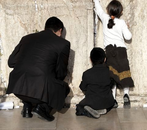 A father and his children place prayers in the Western (Wailing) Wall in Jerusalem.
