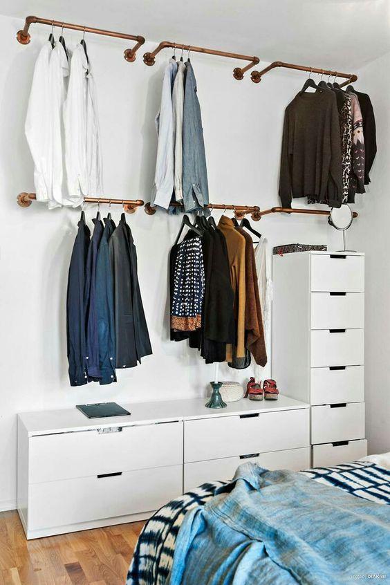 Una idea para organizar tu ropa si no tienes clóset o espacio es poner un rail de madera para colgar tus prendas.