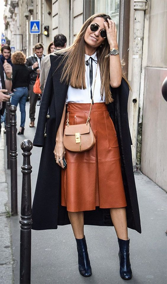 Street style look com saia midi, camisa e sobretudo preto