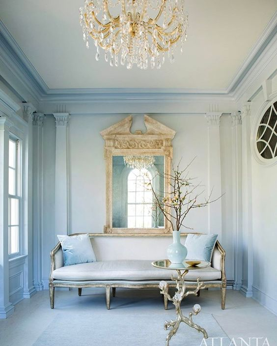 Elegant light blue living room with European style, elaborate moldings, and crystal chandelier. Beautiful Classically Refined Rooms