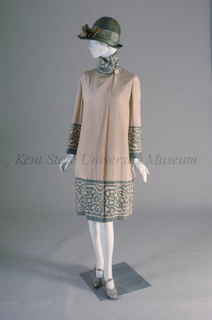 1926-1927 Culture	American Day coat of white silk twill with green cotton applique. Standing collar, side fastening, slim, knee length, green applique in geometric pattern, collar, cuffs and hem