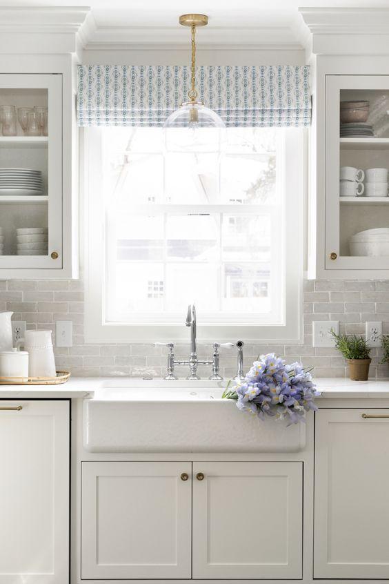 Romantic blue and white serene kitchen design with pops of gorgeous color, farm sink, Shaker cabinets, and subway tile! #kitchendesign #kitchendecor #classic #whitekitchen #farmsink #allwhite #interiordesign #interiordesignideas #bridgefaucet #decoratingideas