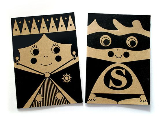 """IONA BINDING - Notebooks that measures 5,70"""" x 8,26"""". Printing on black with a princess and a superhero illustration."""