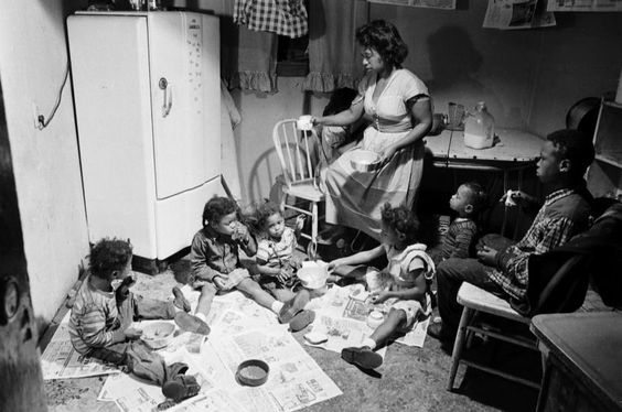 "<strong>Caption from LIFE.</strong> ""In their old home in a dark basement, Mornice Garrett and her seven children eat dinner, chicken necks boiled with spaghetti. Their two rooms lack space for either a dining table or any chairs. Newspapers help cover a floor often damp from faulty drains. At night, the six Garret daughters sleep in one double bed."""