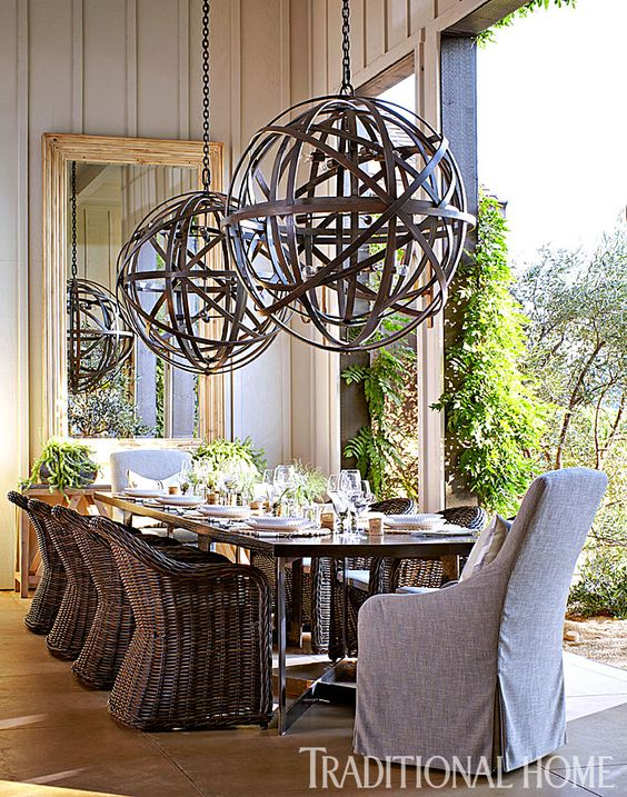 The banquet table in the outdoor dining room is graced by an enormous pair of bronzed chandeliers. - Photo: John Merkl / Design: Hillary Thomas:
