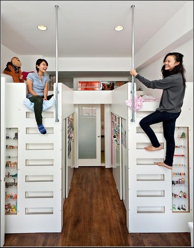Loft beds with walk-in closet space underneath for a shared, two-girl bedroom.