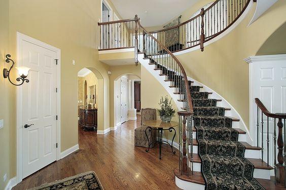 Bogenförmige Treppen mit Teppich-Läufer, die Landung in zwei Geschichte Eingangshalle mit harten Holzfußboden