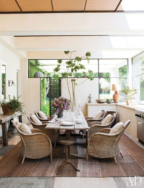 DeGeneres and De Rossi added a screened porch, where a 19th-century trestle table is paired with wicker armchairs.