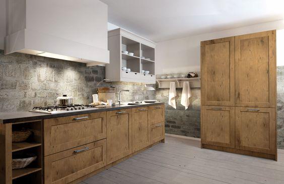 Landelijke keuken met houten keukenkasten. Deze keuken straalt een en al landelijkheid en gezelligheid uit door de materiaalkeuze van de keukenkasten. Ook de muur van deze ruimte zorgt voor een rustieke sfeer.