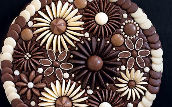 Use chocolate buttons and raisins to create this elaborate floral showpiece. Tässä olisi kunnon suklaa kakku XD Pitäisi aikapaljon tehdä itse noita suklaa nappeja etukäteen jne, että tämä onnistuisi, mutta jonkin tämännäköisen teko on mahdollista. Varoitus, tämä olisi TOSI suklainen