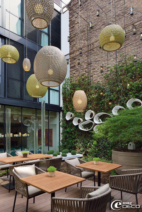 Suspensions 'Dala Lantern' du designer Stephen Burks pour la marque 'Dedon', lanternes 'Loft' de la marque 'Mauduit-Briard', distribuées par 'Idée Concept' à Rennes, fontaines tube en plexiglas chez 'Proviviers', installées par 'Jardin Unique', tables 'Net' et chaises 'Bitta' de la marque 'Kettal'