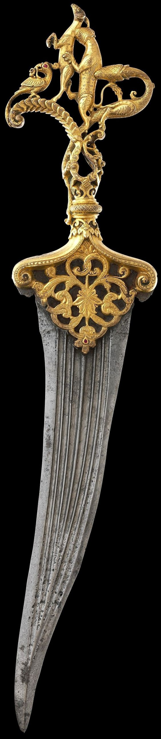 Indian (Deccan, Bijapur or Golconda) dagger, 16th c, cast copper hilt, chased, gilded, inlaid with rubies. Portraits of Sultan 'Ali 'Adil Shah of Bijapur 1558–80 show him wearing similar zoomorphic hilt daggers. In the ruby-studded hilt, a dragon whose tail wraps around the grip attacks a lion, which is attacking a deer, symbolic of the deity Garuda. Before the deer is a bird with a snake in its beak. Lower down is a mythical lionlike Yali, with floral scrolls issuing from its mouth. Met Museum