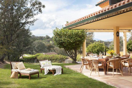 Porche junto al jardín con comedor en madera y fibra natural y tumbonas con cojines