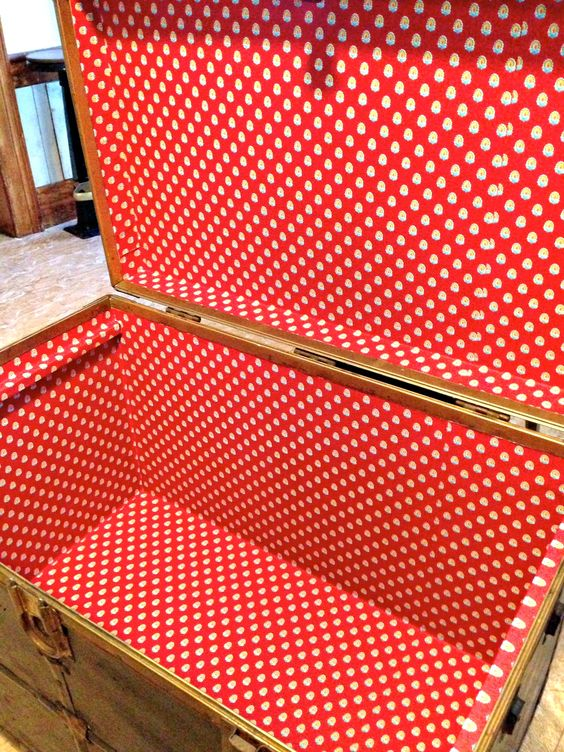 Creating beauty inside a steamer trunk.  Adding wallpaper not only adds beauty, but protects storage as well.