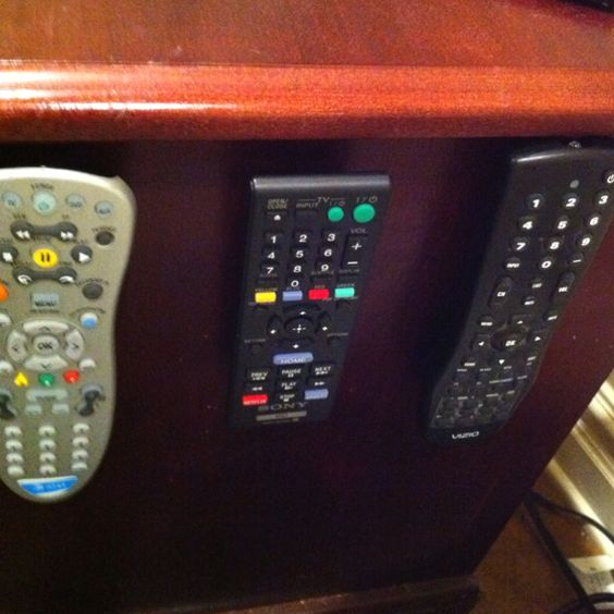Velcro remotes to the side of a nightstand to keep them from cluttering the top of the nightstand or drawers.