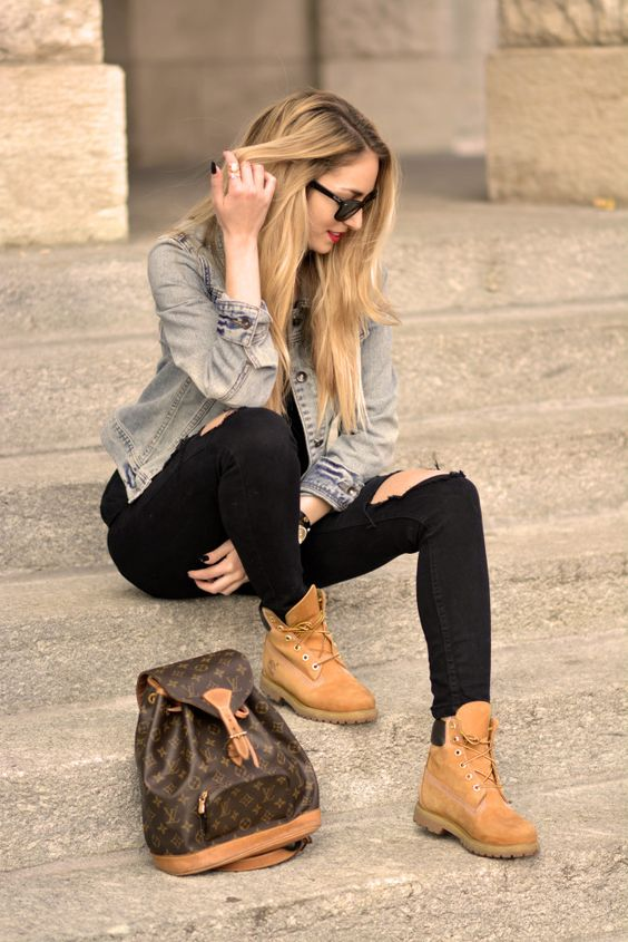 Acheter la tenue sur Lookastic:  https://lookastic.fr/mode-femme/tenues/veste-en-jean-bleu-clair-jean-skinny-noir-bottes-sac-a-dos-brun-fonce/9578  — Sac à dos en cuir imprimé brun foncé  — Veste en jean bleue claire  — Jean skinny déchiré noir  — Bottes en daim brunes claires