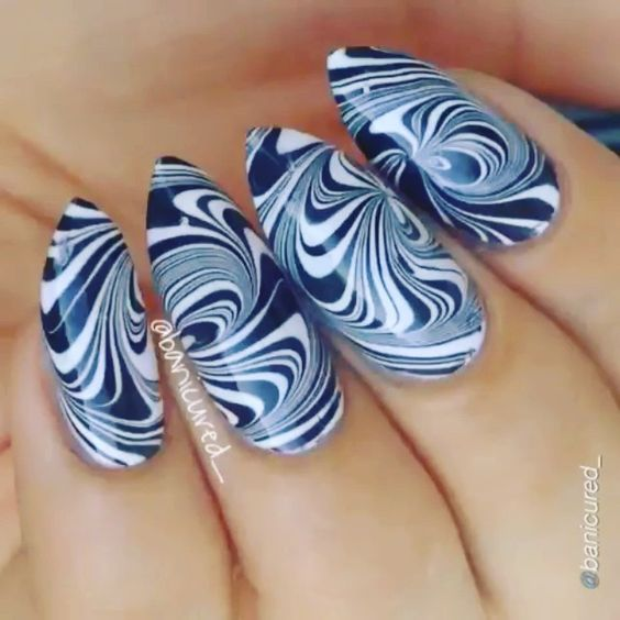 """Nail DIY tutorial. Swirl water marble. By @banicured_ Video for my swirly water marble! I first picked up this technique after following a pictorial posted by miss @mucking_fusser For this design I used @sally_hansen """"White On"""" and """"Black Out"""" polishes. PLEASE read the following steps before asking questions. I also have lots of tips and info on two photos I posted a few weeks back so please check those, too. 1⃣ Start with a small cup and room temperature water. Paint your nails white then…"""