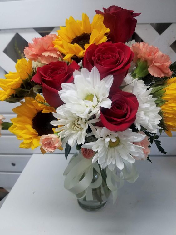 A Vase With Red Roses Orange Carnations Sunflowers And White Daisies Stillingsandembry Roses Red Wine Red Wedding Sunflowers And Roses Flower Delivery