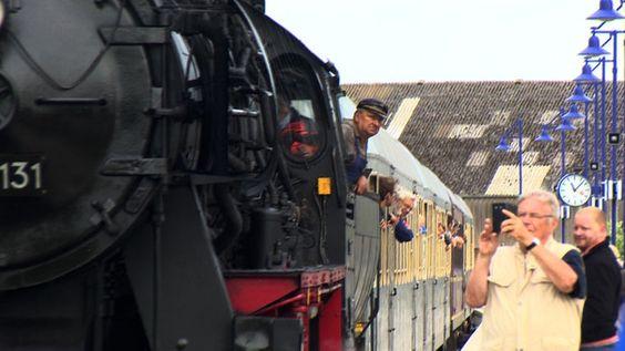 Bild zeigt den Dampfzug der an einem Bahnhof hält.