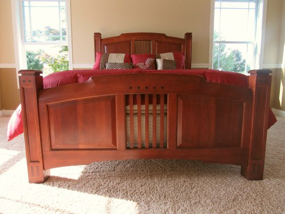 Cherry wood bed frame, single hung windows with grids on each side of the bed. Tan carpet and tan/ gold walls.