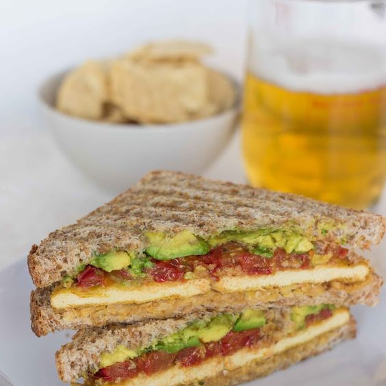 """Smashed Chickpea, Avocado and Roasted Tomato Sandwich with """"Cheesy"""" Tofu Recipe Lunch and Snacks, Main Dishes with bread, tomatoes, olive oil, kosher salt, pepper, garbanzo, cumin, chili powder, onion powder, garlic powder, fresh basil, avocado, tofu, extra firm tofu, olive oil, all purpose unbleached flour, unsweetened almond milk, kosher salt, nutritional yeast, dijon mustard, paprika, black pepper, nonstick spray, olive oil"""
