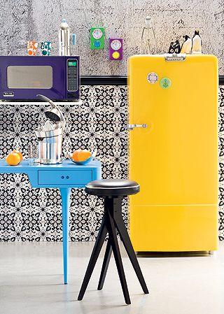 As formas e as cores misturadas deixam a cozinha alegre e divertida. Destaque para os eletrodomésticos que parecem antigos, mas são de última geração. A geladeira Ice Box, por exemplo, é de fibra de vidro e tem pintura automotiva amarela.: