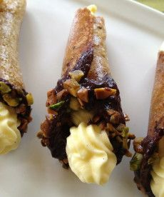 Pistachio Vanilla Tuiles- filled with vanilla bean pastry cream dipped in chocolate garnished with pistachio pieces.