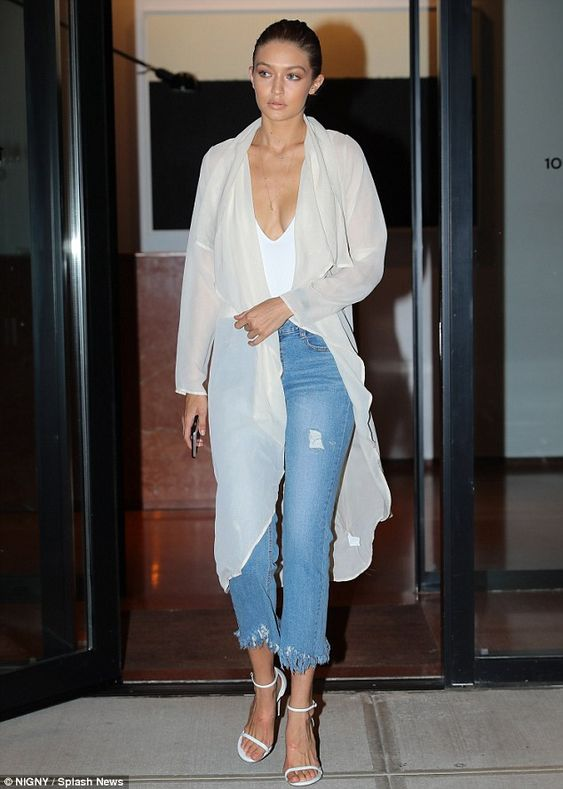 Coming through: The model covered up in a sheer silk cardigan and sported white…